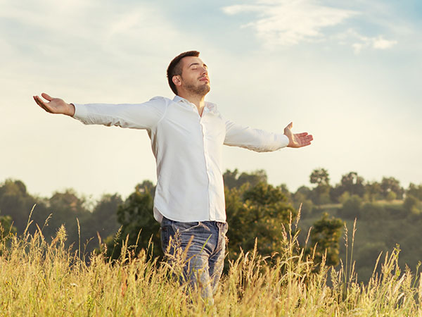 Freedom. Young man with open arms walking through grass. Enjoying in spring - autumn time