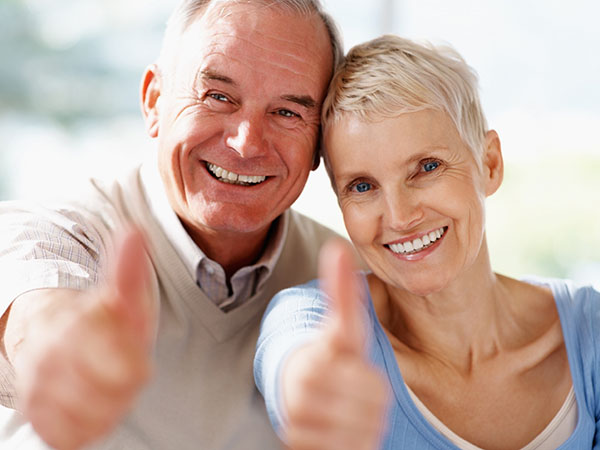 Success -  Portrait of a older couple showing thumbs up